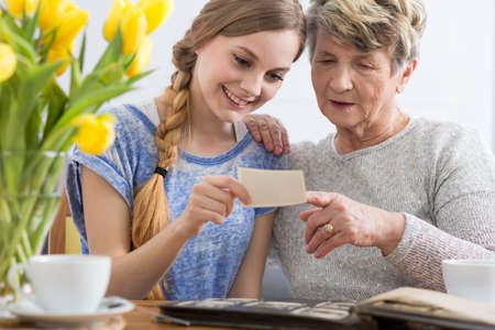in memory: Young girl and grandmother watching together photo album, sitting in cozy interior Stock Photo