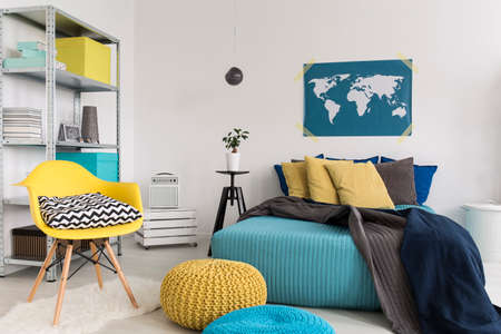 Shot of a modern blue and yellow bedroom