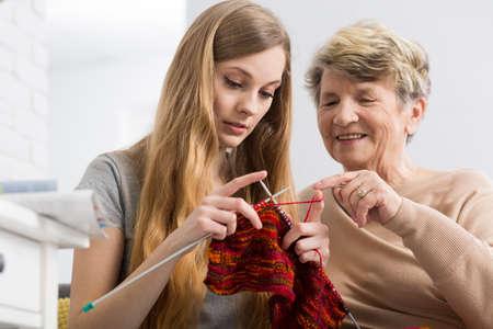 granddaughter: Happy grandmother teaching her granddaughter knitting, smiling
