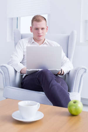 communication occupation: Young man sitting on armchair, working on a laptop in light interior