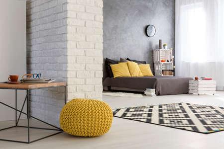 Lichte interieur met witte, decoratieve bakstenen muur, gele poef en ruime slaapkamer
