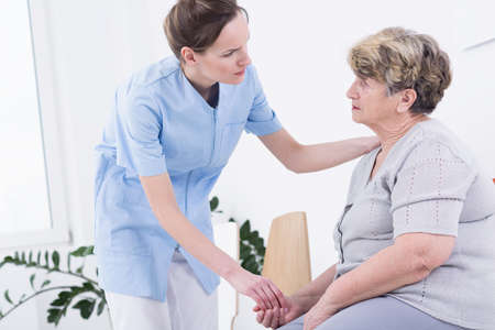 carer: Carer helping senior woman, standing in light interior