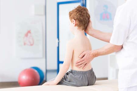 Kisfiú gerincferdülés rehabilitációs klinikára. Gyógytornász dolgozó speciális módszerrel fiú gerincoszlopot