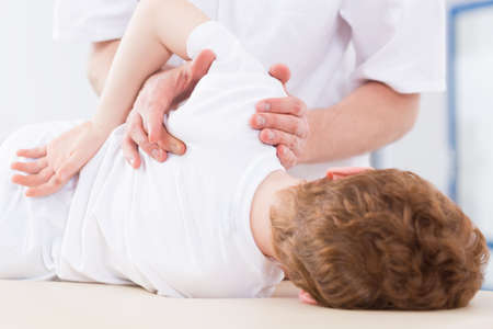 Fysiotherapie specialist oefenen schouder kleine jongen na een blessure