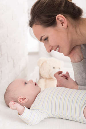 Plan d'une jeune maman heureuse regardant son petit bébé