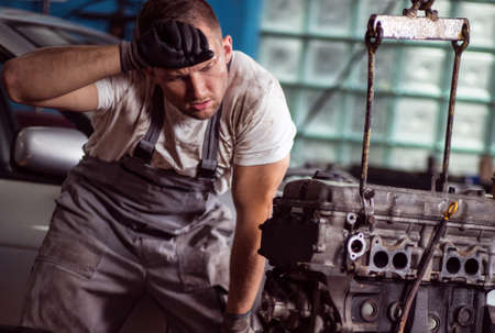 shop skill: Young car mechanic is very tired at his work