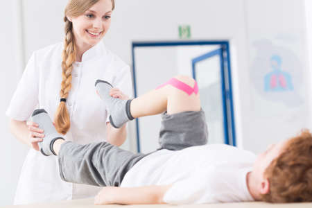 Young pretty smiling physiotherapist exercising with little boy after knee injury