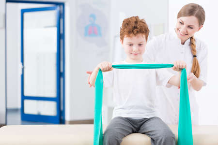 Little red head boy exercising with a elastic band in physical therapy clinic. Next to him young pretty physiotherapist