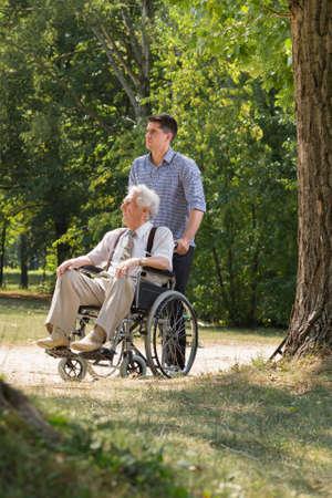 niño empujando: Cuidador y hombre discapacitado caminando en el parque