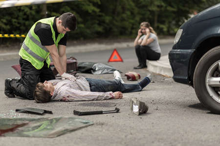Paramedic resuscitating on street car accident victim, in the background woman talking on phone. Stock Photo