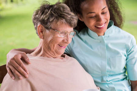 patient care: Young carer and senior woman happy together