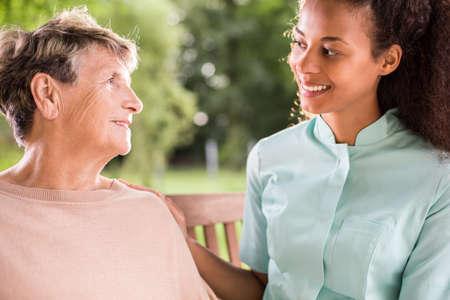 caring nurse: Happy aged woman talking with caring nurse
