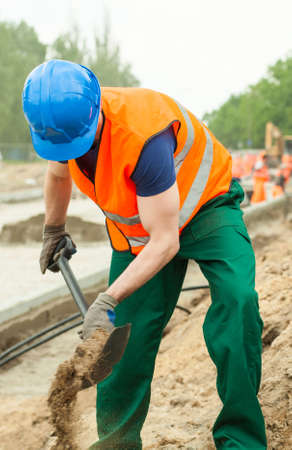 digging: Image of worker digging ground at road construction