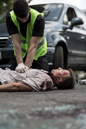 paramedic: Paramedic resuscitating man injured in car accident, car in the background.