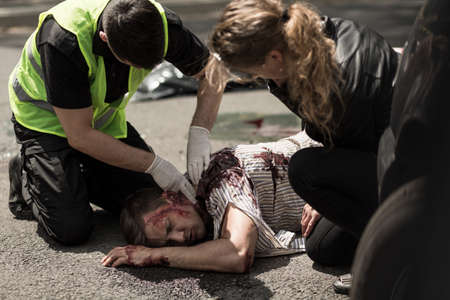 Man and woman giving first aid to injured man lying on street.