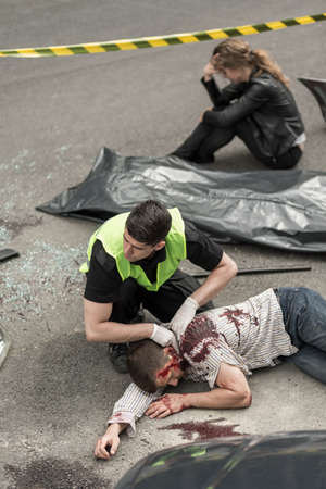 accident body: Man working in the scene of the accident, body lying on street, despair woman sitting in the background Stock Photo