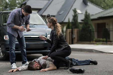Woman helping car accident victim and man with cellphone calling for help.