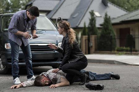 Mujer ayudar a las víctimas de accidentes de coche y el hombre con el teléfono celular para pedir ayuda.