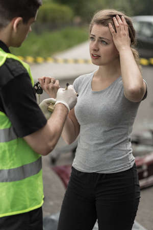 Policeman and young woman giving evidence after car accident. Archivio Fotografico