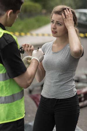 Politieagent en jonge vrouw die het bewijs na auto-ongeluk.