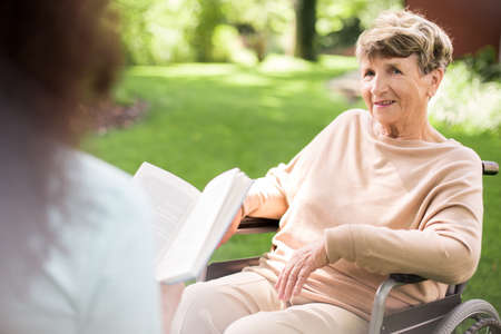 senior woman: Young caregiver reading a book to senior happy woman