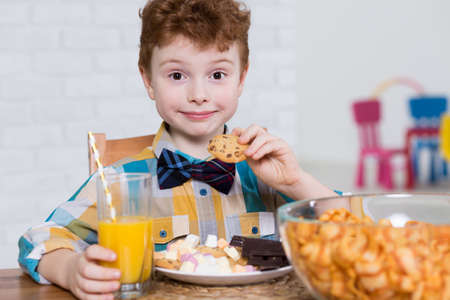 junky: Happy little boy eating cookies and chocolate for dessert. Next to him on the table bowl full of chips and orange juice