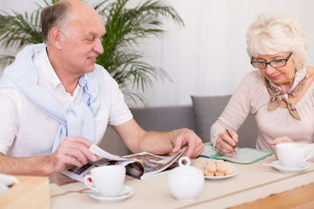 evening newspaper: Older elegant woman doing crossword and senior husband reading newspaper at home