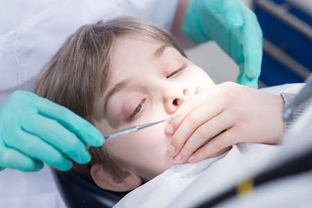 dental fear: Close-up of a little boy in a dental chair about to have a dental procedure, covering his mouth with his hand