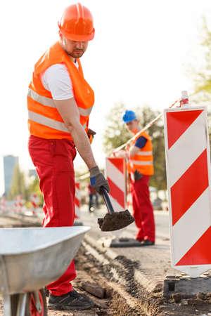 obrero: Imagen del trabajador con la pala en el casco de seguridad de color naranja Foto de archivo