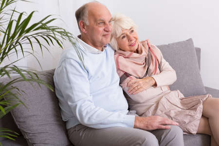 woman couch: Elderly man embracing his elegant woman. Happy couple sitting together on a couch