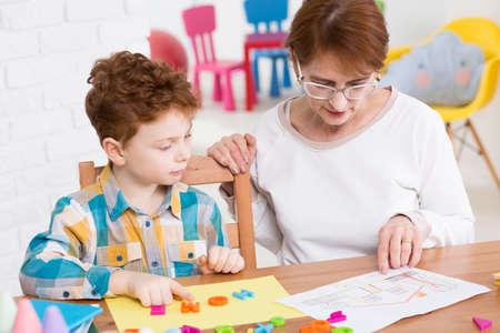 Fiatal fiú új szavakat tanulni játszani színes betűkkel. Régebbi tanár ül mellette