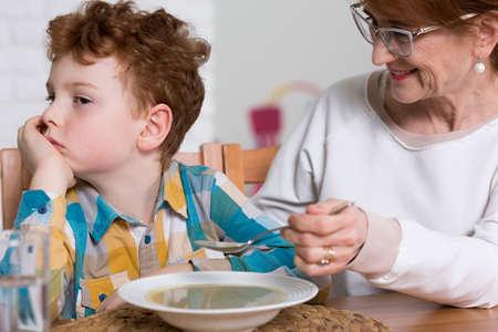 psicologia infantil: abuela introduce a su nieto con sopa sonriendo. Poco exigente con la comida traviesa negarse a comer