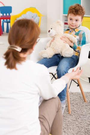 psicologia infantil: chico rebelde joven con el problema de tener TDAH charla con pedagogo. Sentado en una silla de oficina Foto de archivo