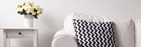 living room sofa: Close up of white room with sofa, pattern pillow, small table and bouquet of white flower in decorative pot Stock Photo