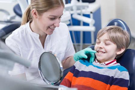 Écolier dans une chaise de dentiste en souriant à un miroir tenu par un assistant dentaire assis à côté de lui