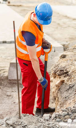 reflective: Photo of man in reflective uniform repairing street