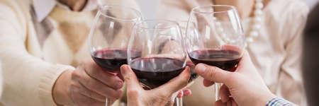 Primer plano de vasos con vino tinto en manos de las personas. Tostar para vacaciones