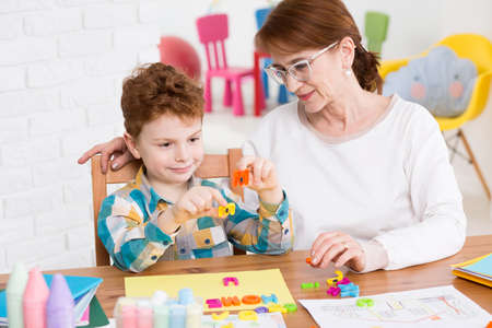 mental disorder: Little happy boy having classes with occupational therapist. Setting words from colorful letters Stock Photo