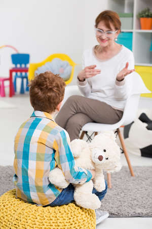 color therapist: Nice school pedagogue talking with little boy having problems with behavior Stock Photo
