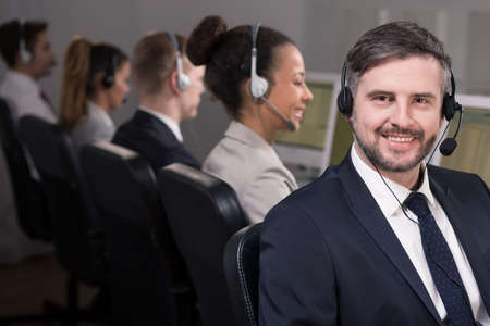 workmate: Shot of a smiling call center agent and his colleagues working in the background