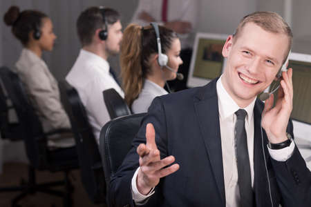 telemarketer: Shot of a young telemarketer laughing talking and with his client Stock Photo