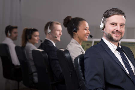workmate: Picture of a smiling call centre consultant and his workmates Stock Photo