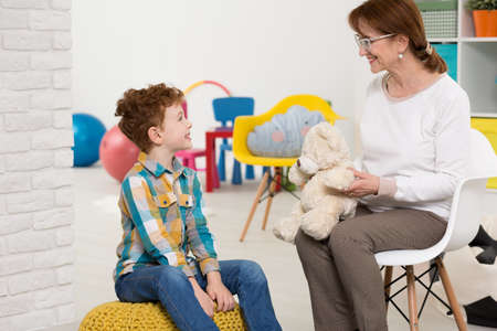 color therapist: Elderly nice psychotherapist working with young autistic boy. Sitting in colorful office with toys
