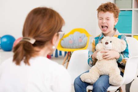 Naughty jonge jongen met ADHD geschreeuw op het kantoor van psycholoog Stockfoto