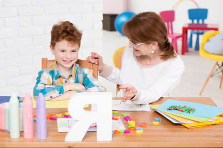 El niño pequeño feliz con trastorno mental que tiene lección de lectura privada con los niños terapeuta Foto de archivo