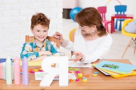 Szczęśliwy chłopiec z zaburzeniami psychicznymi mającą prywatną lekcję czytania z dziećmi terapeuty