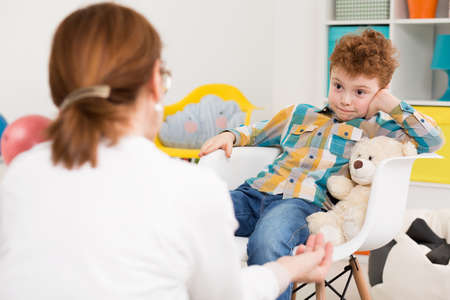 pedagogo que tiene una sesión terapéutica con el muchacho travieso con TDAH