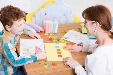color therapist: Happy little boy having speech problem. Speech therapist helping her patient to read