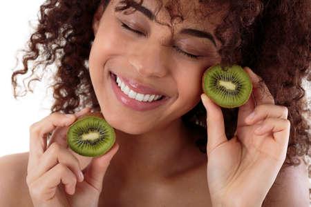 kiwi fruta: Retrato de una mujer afroamericana que sostiene dos piezas de un kiwi, fondo jóvenes, blanco