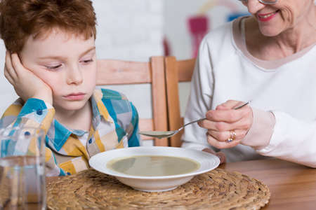 trouble: Little poor eater boy on dinner at grandmothers. Happy grandmother feeding the kid with hot soup